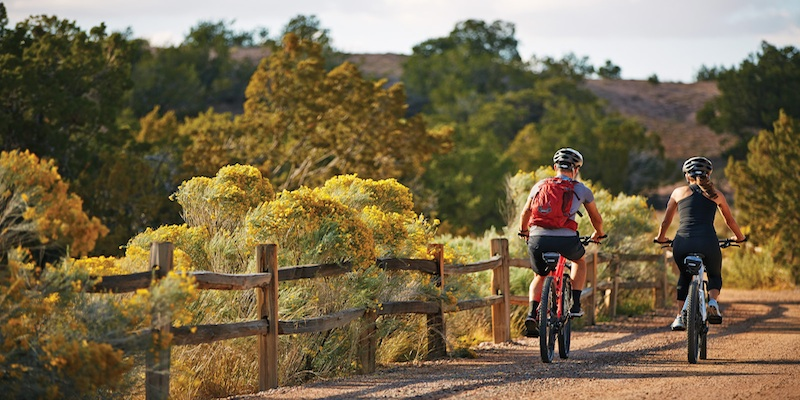 Couple riding bikes through rural countryside near Santa Fe New Mexico