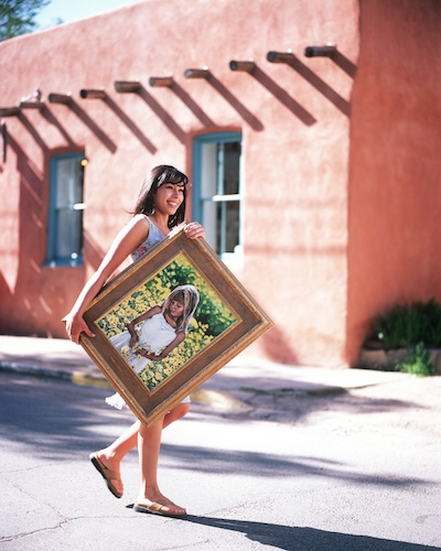 Girl carrying painting in street in Santa Fe