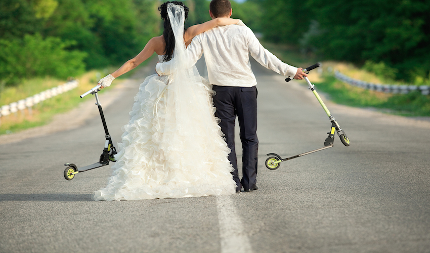 bride and groom walking away with scooters