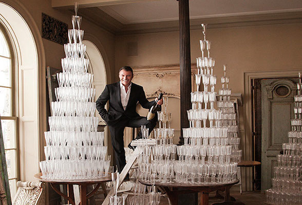 Colin Cowie standing in front of stacked champagne glasses