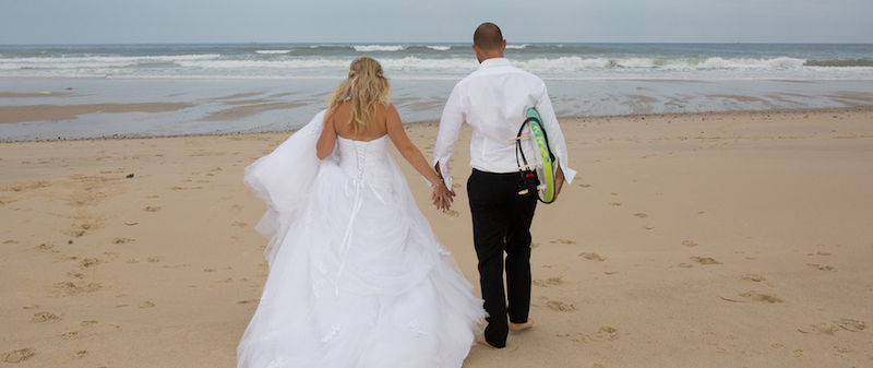Wedding couple with surf board